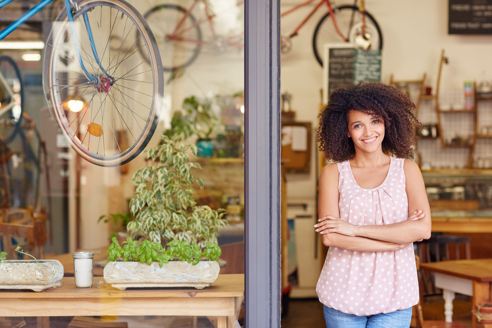 51356645 - young mixed race woman smiling, while standing in the door of her cafe with her arms folded proud to be the owner of a small business